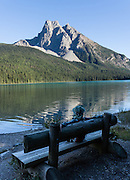 A hiker rests on a bench at Emerald Lake. Mount Burgess (2599 meters or 8527 feet elevation) rises above Emerald Lake in Yoho National Park, British Columbia, Canada. The Emerald Triangle makes a fine hike of 20 km (12 miles, with 3200 feet gain) around Emerald Lake and over Burgess Pass and Yoho Pass. Yoho is one of several Canadian Rocky Mountains parks which comprise a spectacular World Heritage Area listed by UNESCO in 1984.