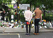 © licensed to London News Pictures. LONDON, UK.  26/07/11. Two men look at flowers and a street sign near to the house. On the day of her funeral fans look at flowers outside the Camden house of Amy Winehouse in North London today (26 July 2011). The singer passed away on Saturday 23th July. Mandatory Credit Stephen Simpson/LNP