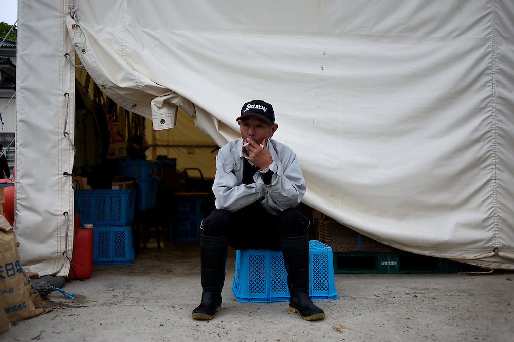 May 28, 2013 - Togura, Japan: A fisherman of Togura, smokes a cigaret outside a storage shed in the local port after collecting ropes used to grow sea weed. Togura, a small fishing village in Minami Sanriku, was vastly destroyed by the 2011 tsunami that hit the northeast coast of Japan. Thousands died and hundreds of families lost their houses, business and boats. The recovering community works now in a cooperative system where the few remaining boats, spared by the tsunami, are shared by all. (Paulo Nunes dos Santos)