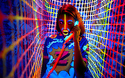 Young girl wearing glowing shirt talks on glowing phone standing inside glowing fence.Black light