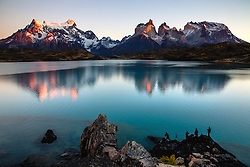 Photographers photographing the majestic peaks and spires of Torres del Paine reflected on a blue lake at dawn, Torres del Paine, Chile, South America
