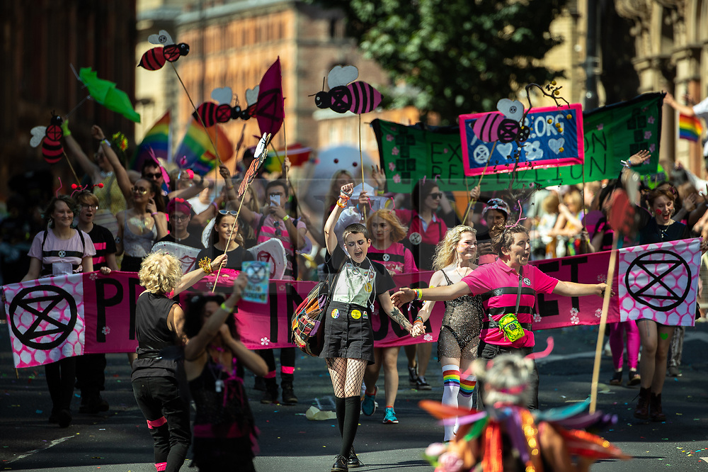 """© Licensed to London News Pictures . 24/08/2019. Manchester, UK. Extinction Rebellion """" Pride in our Planet """" banner . The 2019 Manchester Gay Pride parade through the city centre , with a Space and Science Fiction theme . Manchester's Gay Pride festival , which is the largest of its type in Europe , celebrates LGBTQ+ life . Photo credit: Joel Goodman/LNP"""