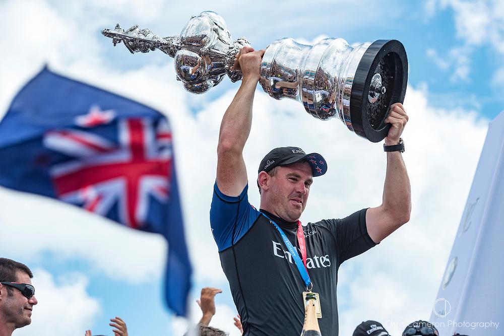 The America's Cup Village, Bermuda, 26th June 2017. Emirates Team New Zealand Sailor / Cyclist Joe Sullivan with the America's Cup.
