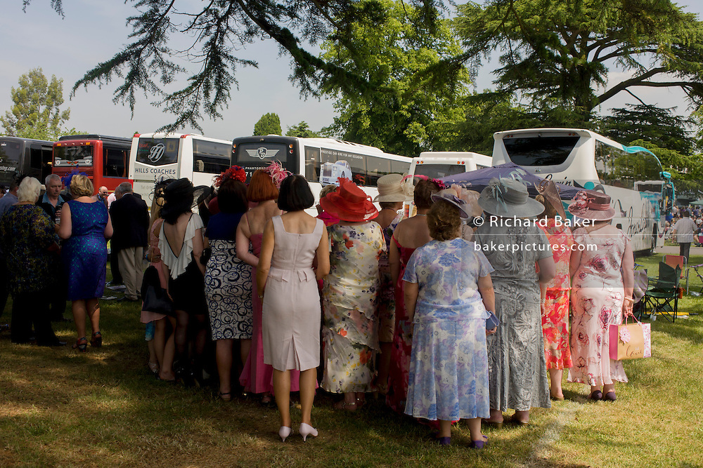 A womens' daytrip group from Wales enjoy a summer's morning, hours before horse racing starts during the annual Royal Ascot festival in Berkshire, England. Royal Ascot is one of Europe's most famous race meetings, and dates back to 1711. Queen Elizabeth and various members of the British Royal Family attend. Held every June, it's one of the main dates on the English sporting calendar and summer social season. Over 300,000 people make the annual visit to Berkshire during Royal Ascot week, making this Europe's best-attended race meeting with over £3m prize money to be won.