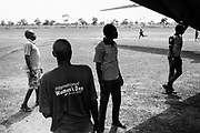 "YIDA, SOUTH SUDAN – JUNE 9, 2018: Aid is delivered by cargo plane to the Yida airstrip.<br /> <br /> Founded in 2011 by Samaritan's Purse, and strategically located near the border with Sudan to the north, the Yida ""host community"" was originally established to provide refuge for for the thousands of Nuba fleeing persecution by the Sudan government in the nearby Nuba Mountains. Within three years, Yida had grown to a population of 75,000 – representing refugees from across the region. Two additional refugee camps, Adjuonthok and Pamir, were then created to disperse the steady influx of refugees fleeing conflict."