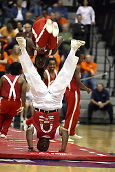 20 March 2010: Illinois Secretary of State and and organizer of the Jesse White tumblers does a handstand as this troupe flies past. The Flying Dutch of Hope College fall to the Bears of Washington University 65-59 in the Championship Game of the Division 3 Women's NCAA Basketball Championship the at the Shirk Center at Illinois Wesleyan in Bloomington Illinois.