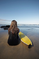 Woman sitting by surfboard on beach back view