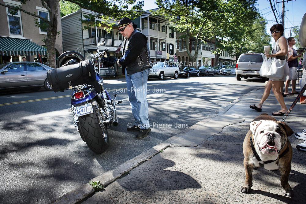 Verenigde Staten.Piermont.New York State. Rockland. 8 juli 2005.<br /> Straatbeeld in het centrum van Piermont, een dorpje aan de rivier de Hudson zo'n 30 km buiten New York city.<br /> Op de foto een motorrijder stapt op zijn Harley Davidson op een doorlopende straat in het centrum van het dorpje.Rechts een Bulldog van een winkelende bewoner.<br /> Archives 2005, in the streets of Piermont, New York USA.