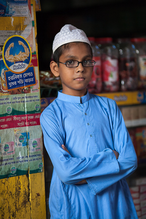 A young Muslim boy leans against the doorframe of a local store in the historical old city of Dhaka, the labyrinth of streets that makes up the oldest part of the city.