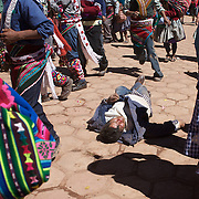 An injured villager lies unconscious and badly injured, after fighting between rival villages in the streets of Macha during the Tinku Festival. Macha, Bolivia, 4th May 2010, Photo Tim Clayton ..Each May, up to 3000 thousands indigenous Bolivian indians descend on the isolated mountainous village of Macha 75 miles north of Potosi in the Bolivian Andes. The 600 year old pre-hispanic Bolivia Festival of Tinku sees villagers from all over the region march into town to be pitted against each other in a toe to toe fist to fist combat.. They dance and sing in traditional costume and drink 96% proof alcohol along with chicha, a fermented beverage made from corn. Townspeople and sometimes the police oversee proceedings who often use tear gas to try and control the villages, whipped into a fighting frenzy by the dancing and alcohol, but as the fiesta goes on things often escalate beyond their control, with pitched battles between rival villages break out,  The blood spilt is an offering to the earth goddess - Pachamama - to ensure a good harvest for the coming year. Over the years dozens have died, yet the rite continues.