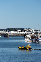 A Whale watching tour boat filled with tourists motors along the Inner Harbour of Victoria, BC  with the Johnson Street Bridge in the background.