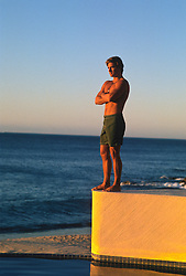 Man with crossed arms standing on the edge of a swimming pool overlooking the Pacific Ocean in Mexico