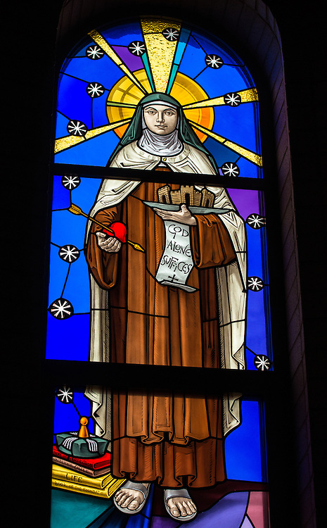 "A stained glass image of St. Teresa of Avila, Carmelite nun, mystic and doctor of the church, at the Carmelite monastery in Denmark, Wis. Teresa holds a scroll with the words, ""God alone suffices,"" the final line of her 16th-century prayer called St. Teresa's Bookmark. According to tradition, Teresa carried the bookmark around in her prayer book, where it was found after her death in 1582. (Sam Lucero photo)"