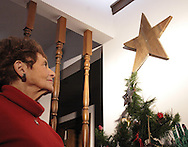 "Marolyn Ray looks at a wooden star from her grandparents farm near Spencerville, Ohio.  The star, 16"" inches tall, and around 100 years old, was high on the south side of the barn, and she says, ""when the farm was sold my Dad rescued the star.  One of the tips was broken off, but he made a new piece for it, making it even more special."""
