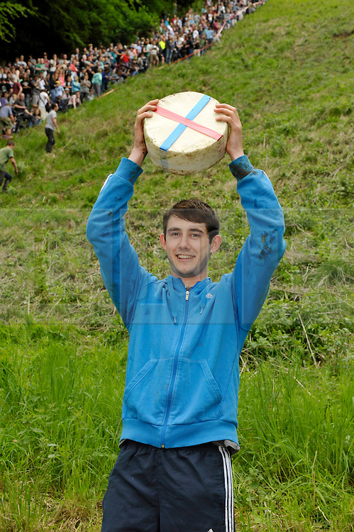 &copy; Licensed to London News Pictures. 26/05/2014; Brockworth, Gloucestershire, UK.  Josh Shepherd age 19 from Brockworth, winner of the first men's race, in the annual custom of Cheese Rolling down Cooper's Hill, with participants chasing a double Gloucestershire cheese down a very steep slope.<br /> Photo credit: Simon Chapman/LNP