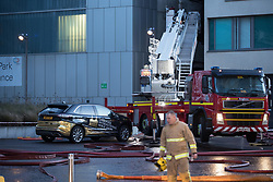 © Licensed to London News Pictures . 01/01/2018. Liverpool, UK. Scene at the Liverpool Echo Arena car park where firefighters are working to extinguish a fire that started late on New Year's Eve and that destroyed all 1,400 cars parked in the multi-story car park. The Liverpool International Horse Show taking place at the Arena was abandoned and people and horses evacuated as dozens of fire crew worked to control the blaze . Photo credit: Joel Goodman/LNP