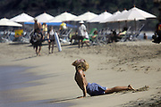 "SHOT 2/11/09 10:46:16 AM - A beach goer performs yoga on the beach in Sayulita, Mexico. Sayulita is a small fishing village about 25 miles north of downtown Puerto Vallarta in the state of Nayarit, Mexico. Known for its consistent river mouth surf break, roving surfers ""discovered"" Sayulita in the late 60's with the construction of Mexican Highway 200. Today, Sayulita is a prosperous growing village of approximately 4,000 residents. Hailed as a popular off-the-beaten-path travel destination, Sayulita offers a variety of activities such as horseback riding, hiking, jungle canopy tours, snorkeling and fishing. Still a mecca for beginner surfers of all ages, the quaint town attracts upscale tourists with its numerous art galleries and restaurants as well. Sayulita has a curious eclectic quality, frequented by native Cora and Huichol peoples, travelling craftsmen as well as international tourists. Sayulita is the crown jewel in the newly designated ""Riviera Nayarit"", the coastal corridor from Litibu to San Blas. It's stunning natural beauty and easy access to Puerto Vallarta have made Sayulita real estate some of the most sought after in all of Mexico..(Photo by Marc Piscotty / © 2009)"