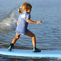 SURF SCHOOL FOR KIDS IN MAURITIUS. JESSICA, SEVEN YEARS OLD GIRL TAKES HIS FIRST WAVE AND SHE LIKES IT
