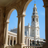 Basilica of Nossa Senhora de Rosário in Fátima, Portugal<br /> On May 13, 1917, the Blessed Mary appeared to three children while they tended their sheep in a field called Cova da Iria. This same apparition occurred for the next five months until about 70,000 people witnessed the last occasion. Through this colonnade arch is the Basilica of Nossa Senhora de Rosário which honors the miraculous apparitions that occurred at the Sanctuary of Our Lady of Fátima.
