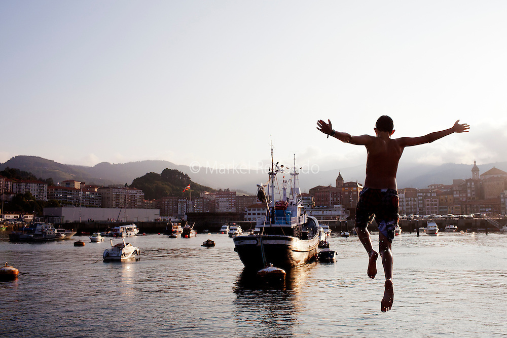 A boy jums into the water at the fishing port of Bermeo.