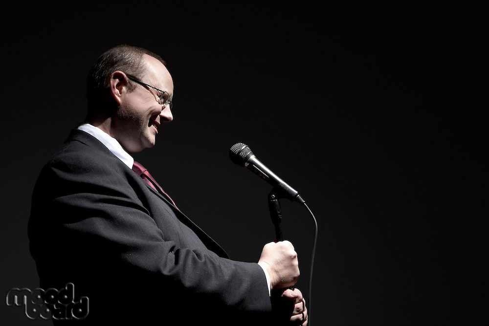 Smiling man in full suit holding microphone side view