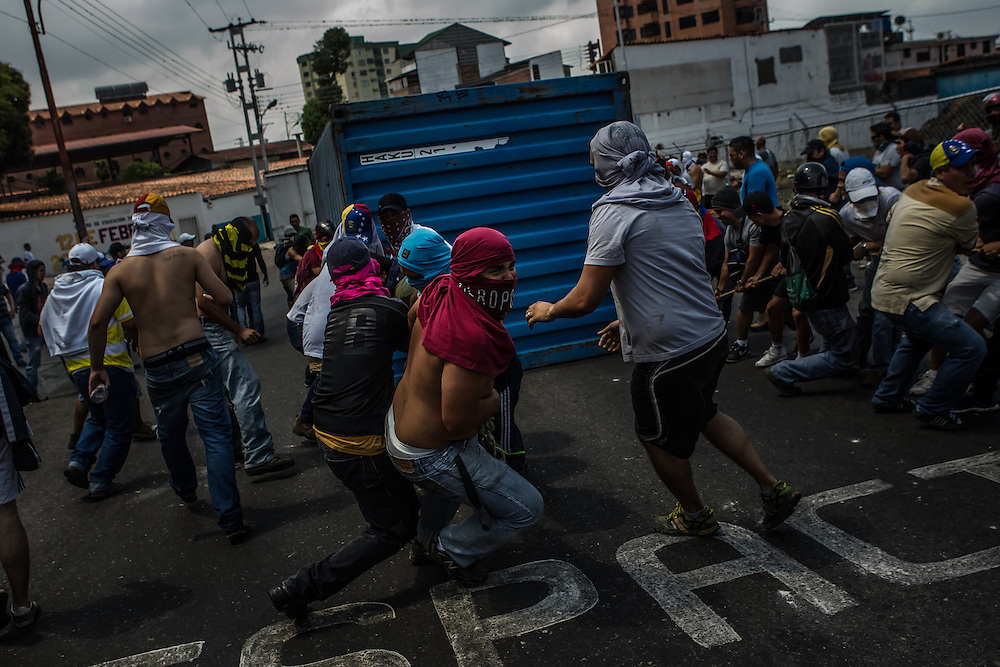 SAN CRISTOBAL, VENEZUELA: Men pull a shipping containter up a 100 yard incline to be used as a barrier in the Las Pilas area of San Cristobal. Las Pilas is one of the hardest hit areas of the protests in all of Venezuela. Anti-government protesters have taken to the streets, constructing barriers on nearly every block, completely gridlocking the city, to protest high inflation, high crime rates and shortages of basic goods, among other things. The protests in Venezuela began in San Cristobal, in the western state of Tachira, and are recognized as being the strongest in the country.   CREDIT: Meridith Kohut for The New York Times
