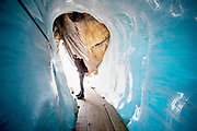 Glaciologist David Volken inside the ice tunnel.. Huge fleece blankets cover parts of the Rhone Glacier in Switzerland in an attempt to stall the inevitable melting of the snow and ice. After a winter with record amounts of snow, most of it was gone when this image was taken on July 14th 2018, exposing the darker ice. While snow is a brilliant reflector of the energy from the sun, the darker ice absorbs the energy instead, accelerating the melting of the glacier. The color and darkness of glacier ice vary all over the world, depending on build-up of pollution, age of the ice, particles picked up by the ice and by microorganisms in the ice. The glacier ice is however rarely white as snow. With shorter winters and vanishing snow cover, the melting of the glaciers is accelerating.