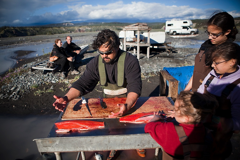 Carlos Rivera, from Wasilla, joined by his three daughters (front to back) Maia, Juliane and Kristian, filets sockeye salmon caught in the family's fish wheel on the Copper River, near Chitina, Alaska. Parmenter and Liana Welty watch, and would later receive a gift of salmon that would be delicious camp dinner for the next two nights.