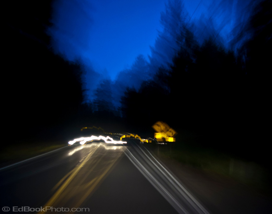 an abstract image of a road in the forest at night