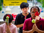 10 JULY 2018 - NAKHON PATHOM, THAILAND:  People pray at Phra Pathom Chedi in Nakhon Pathom. Nakhon Pathom is about 35 miles west of Bangkok. It is one of the oldest cities in Thailand, archeological evidence suggests there was a settlement on the site of present Nakhon Pathom in the 6th century CE, centuries before the Siamese empires existed. The city is widely considered the first Buddhist community in Thailand and the nearly 400 foot tall Phra Pathom Chedi is considered the first Buddhist temple in Thailand.    PHOTO BY JACK KURTZ