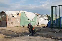 "Calais, Pas-de-Calais, France - 16.10.2016    <br />     <br />  A refugee brush his teeth  in front of a booth with the slogan British Hotel in the ""Jungle"" refugee camp on the outskirts of the French city of Calais. Many thousands of migrants and refugees are waiting in some cases for years in the port city in the hope of being able to cross the English Channel to Britain. French authorities announced that they will shortly evict the camp where currently up to up to 10,000 people live.<br /> <br /> Ein Fluechtling putzt sich die Zaehne vor einer Huette mit der Aufschrift ""British Hotel"" im ""Jungle"" Fluechtlingscamp am Rande der franzoesischen Stadt Calais. Viele tausend Migranten und Fluechtlinge harren teilweise seit Jahren in der Hafenstadt aus in der Hoffnung den Aermelkanal nach Großbritannien ueberqueren zu koennen. Die franzoesischen Behoerden kuendigten an, dass sie das Camp, indem derzeit bis zu bis zu 10.000 Menschen leben Kürze raeumen werden. <br /> <br /> Photo: Bjoern Kietzmann"