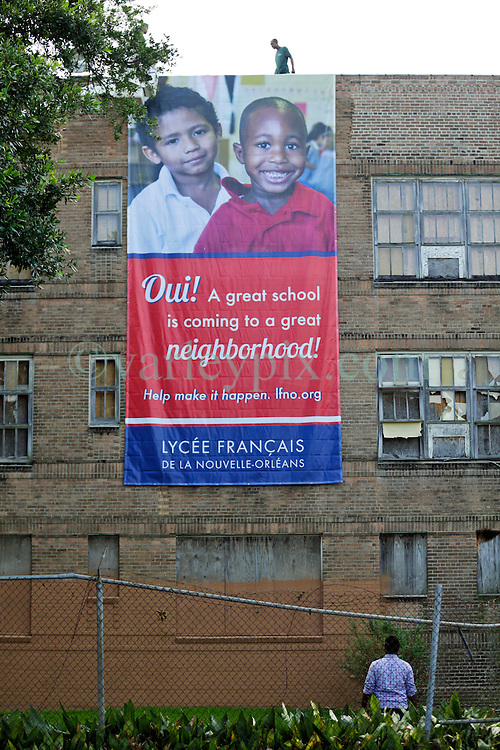 08 August 2015. New Orleans, Louisiana.<br /> Clean up begins at the Alfred C Priestley Junior High School. Lyc&eacute;e Francais installs new fencing, cuts back hazardous trees and hangs a large welcome banner at the derelict old school in Pigeon Town.The last students and teachers left the building in 1980.<br /> Photo; Charlie Varley/varleypix.com