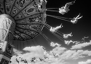 An ethereal whimsical view of people on a swing ride at a state fair.