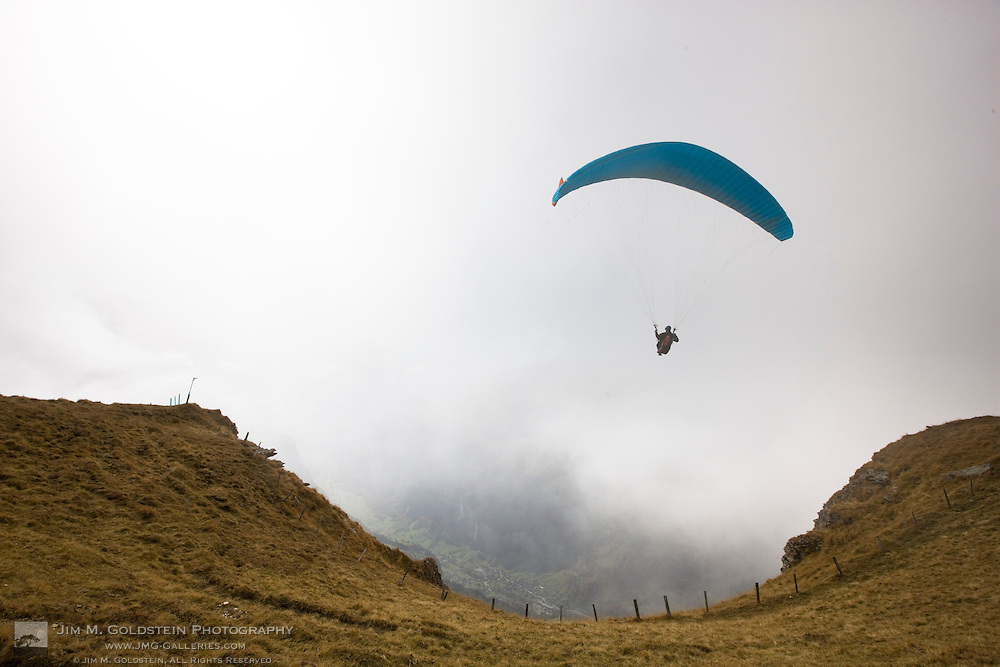 A paraglider takes off into the clouds and glides over Lauterbrunnen with Staubbach Fall in the distance