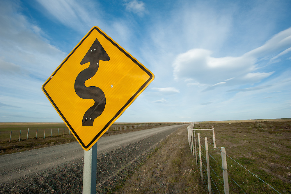 Sign for curving Gravel Road patagonia Chile