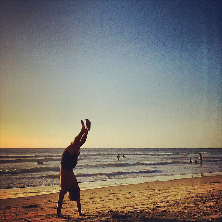 Young man doing hand stand on beach at Del Mar Beach, CA at Sunset