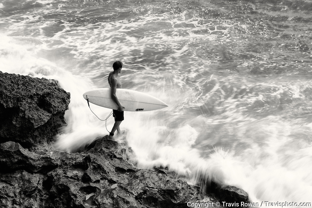 A surfer enters the water at Bingin on the island of Bali.