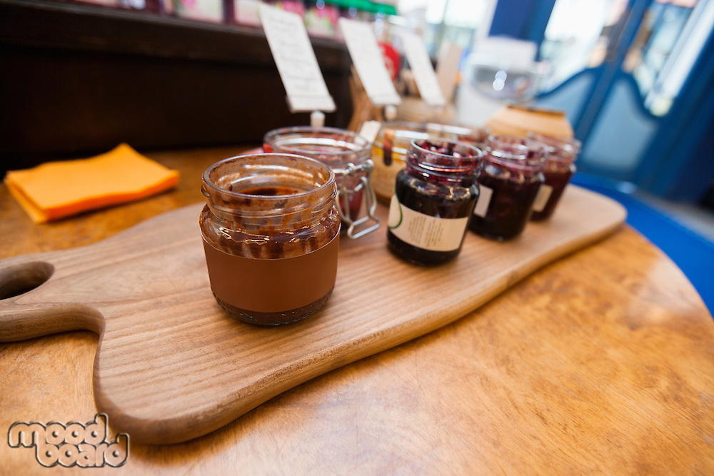 Jars of preserves on cutting board in grocery store