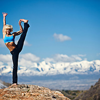 Woman performs Utthita Hasta Padangustasana yoga position in Big Cottonwood Canyon, Utah