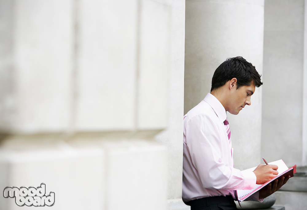 Businessman sitting against pillar outside building writing in notebook