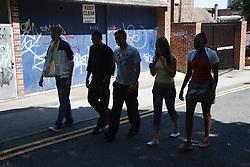 Teenagers walking down the street in shadow.