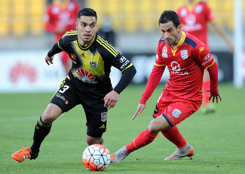 Phoenix's Justin Gulley, left and Adelaide United's Sergio Cirio contest the ball in the A-League football match at Westpac Stadium, Wellington, New Zealand, Friday, November 13, 2015. Credit:SNPA / Ross Setford