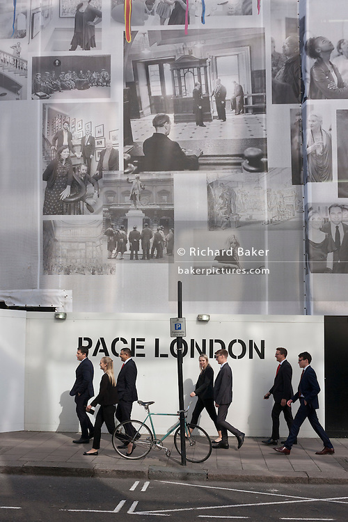 Pedestrians walk below a large construction hoarding for the Royal Academy in central London, England.