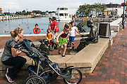 """Annapolis, Maryland - June 05, 2016: Families play by the Kunta Kinte-Alex Haley Memorial statue in historic Annapolis Sunday June 5th, 2016. Earlier that day a perigean spring tide brought some of the highest water levels of the year to the coastal town and partially flooded the park. Pictured are Cate Miller DeMartino, foreground, from McLean, Va., her two daughters, Emery DeMartino, 4, standing on the middle statue, and Catie DeMartino, 8, holding the statue's hand, and Payton Womble, also 4, from Severna Park, Md., seen jumping onto the wall.<br /> <br /> <br /> A perigean spring tide brings nuisance flooding to Annapolis, Md. These phenomena -- colloquially know as a """"King Tides"""" -- happen three to four times a year and create the highest tides for coastal areas, except when storms aren't a factor. Annapolis is extremely susceptible to nuisance flooding anyway, but the amount of nuisance flooding has skyrocketed in the last ten years. Scientists point to climate change for this uptick. <br /> <br /> <br /> CREDIT: Matt Roth for The New York Times<br /> Assignment ID: 30191272A"""