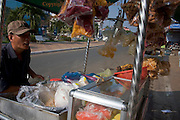 A man is serving fresh fruit from a mobile food cart to a female customer on a city street in Kampong Cham, Cambodia.