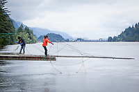 A Kim Brigham and her daughter pull salmon from their gill nets on their families' platform.  Bonneville Dam in the background. Indian Fishers at Cascade Locks near Portland, Oregon fish for Salmon on platforms that have been in their family for generations.  The Indians are the only peoples with permits to fish this way on the Columbia River.  They sell fresh Salmon to buyers from the area.  They use traditional dip net and gill net fishing.
