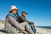 Senior couple enjoy the waterfront view at Long Point Beach, West Tisbury, Martha's Vineyard, Massachusetts, USA.