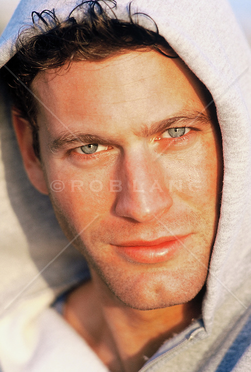 Close up of a good looking man in a hooded sweatshirt