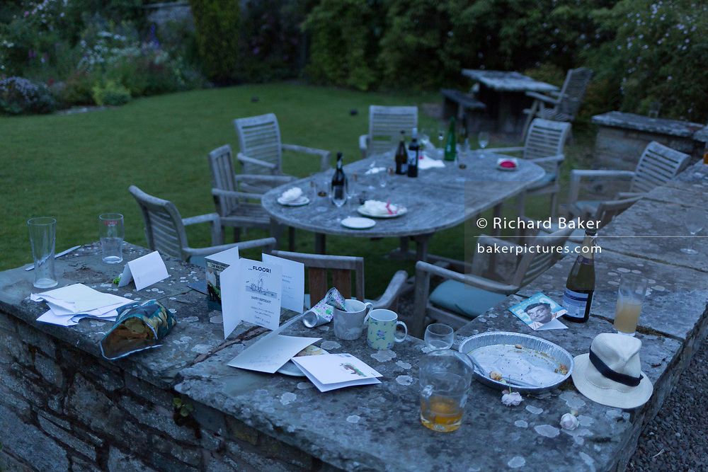 The aftermath debris of glasses, bottles and plates at dawn, the morning after a 50th birthday party, spread around the garden in the Herefordshire countryside, on 23rd June 2019, in Kington, Herefordshire, England.