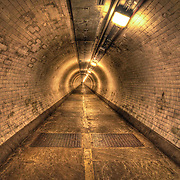 The Greenwich Foot Tunnel crosses beneath the River Thames, linking Greenwich in the south with the Isle of Dogs to the north. Designed by Sir Alexander Binnie, the Tunnel opened in August 1902 so that south London residents could go to work in the docks on the Isle of Dogs.<br />